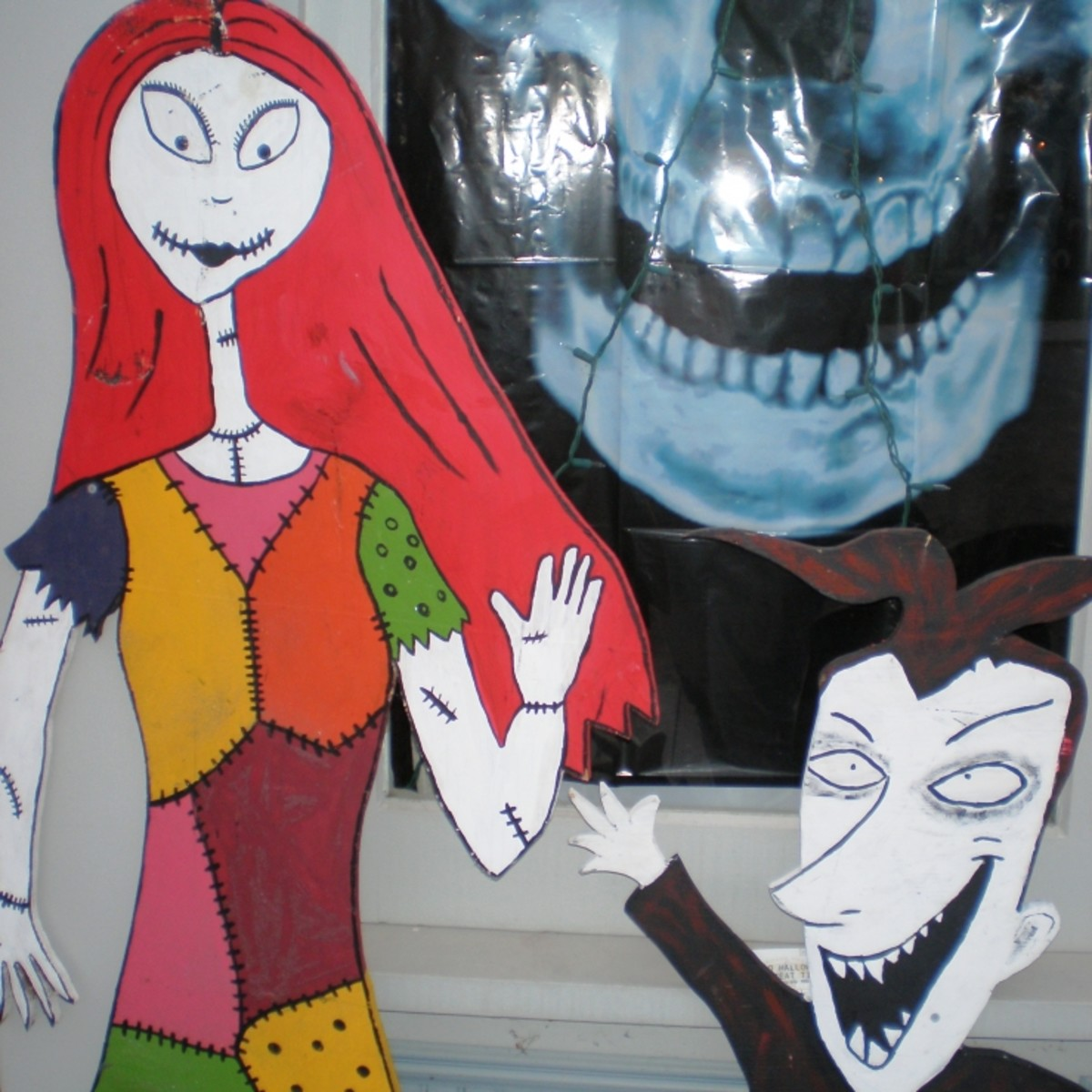 Halloween decor like Sally and Lock from The Nightmare Before Christmas wave to guests.