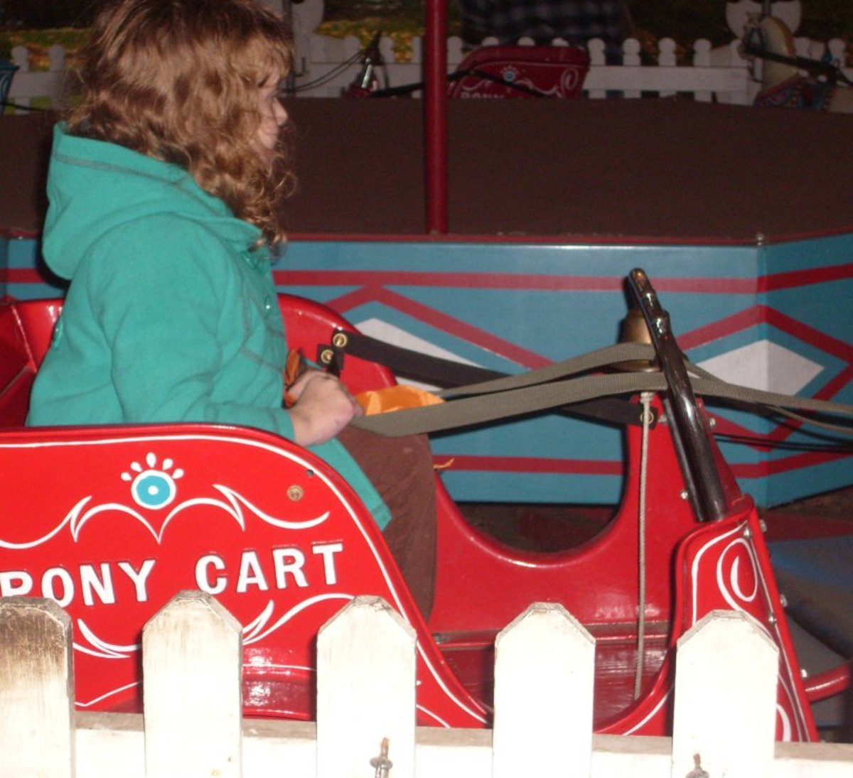 A young girl enjoys the Pony Carts, one of several vintage amusement park rides at Crossroads Village.