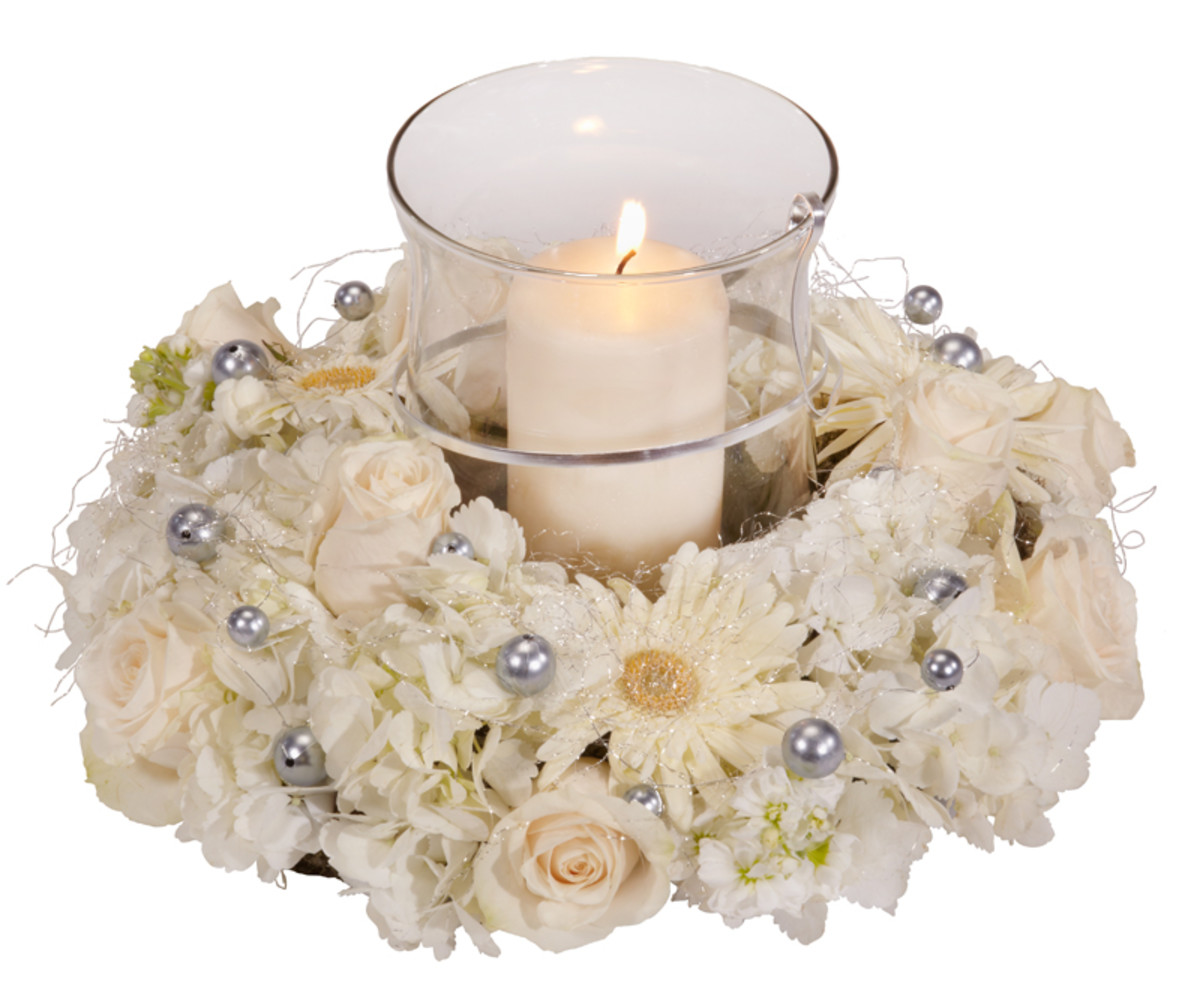 A hurricane vase wih pillar candle, surrounded by a foam ring filled with flowers and accented with oasis mega beads.