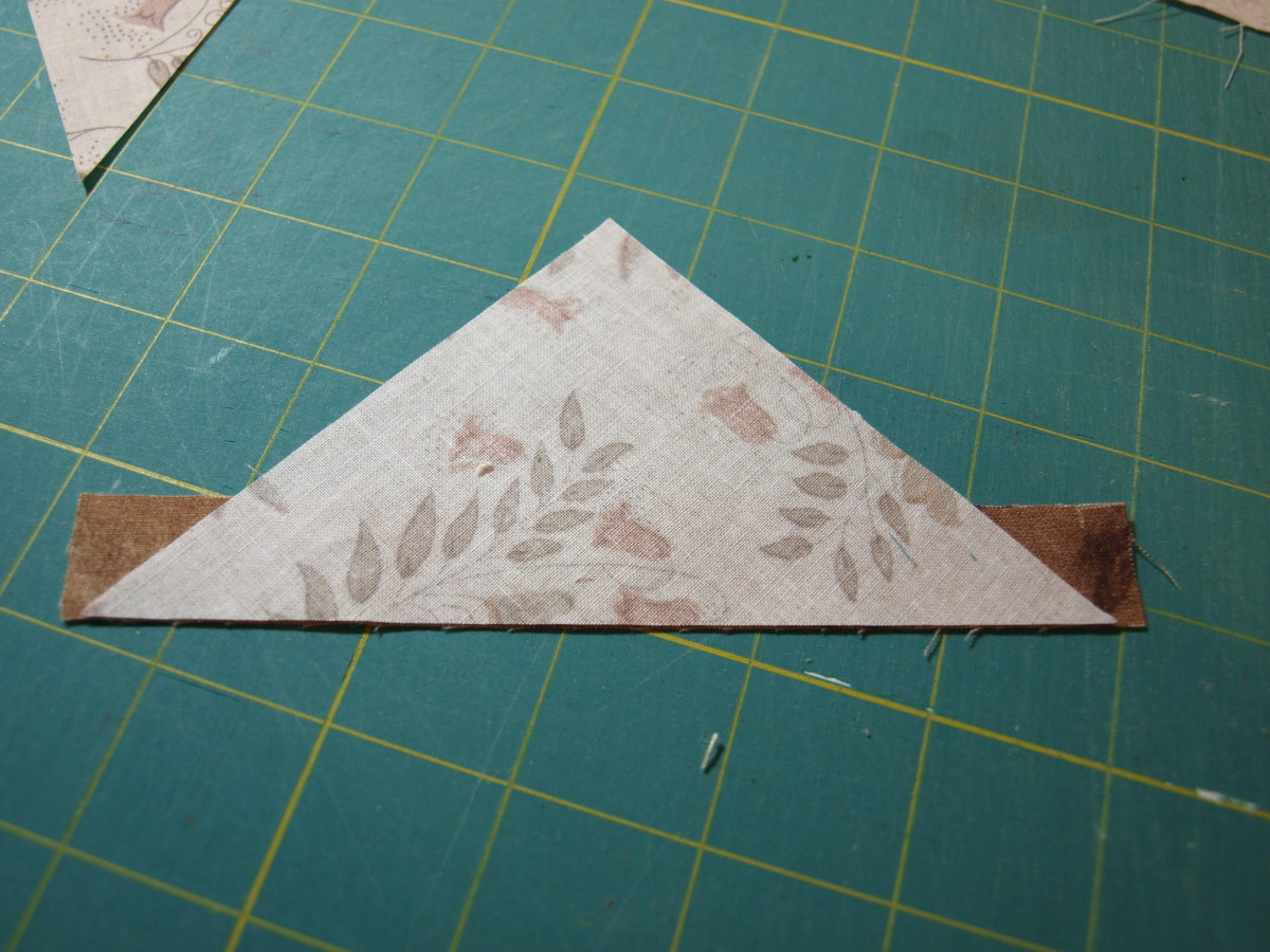 "2. Center the strip to the diagonal cut and sew together, using a 1/4"" seam.  Sew the other triangle to the other side of the strip."