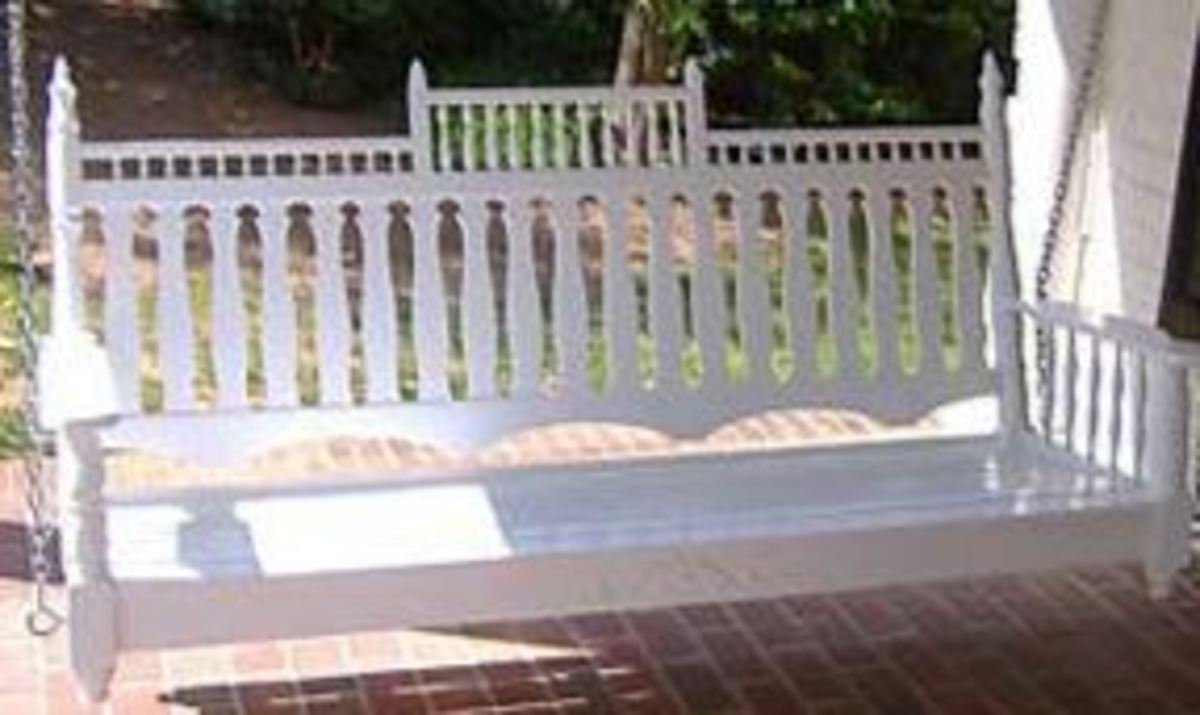 white Victorian porch swing with decorative slats and filigree at the top