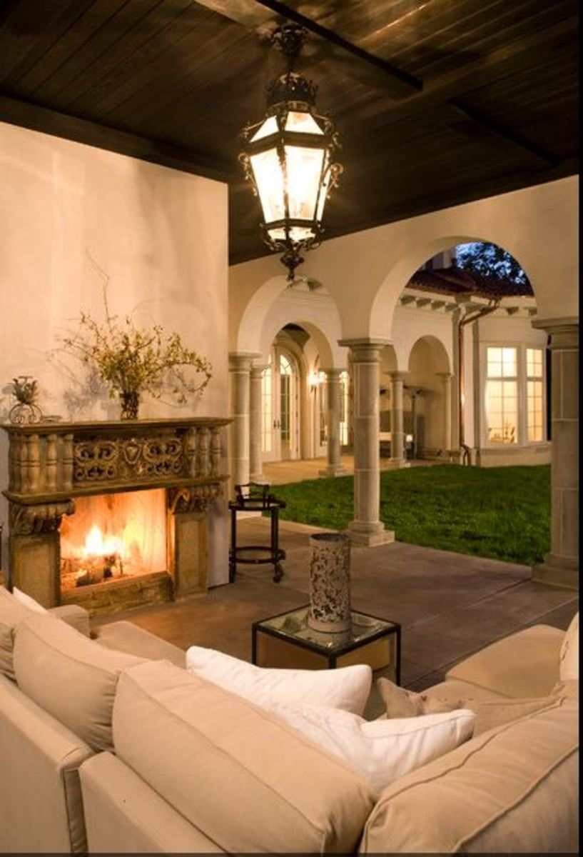 Mediterranean patio with outdoor fireplace, romantic ceiling light and pillars accent an outdoor couch