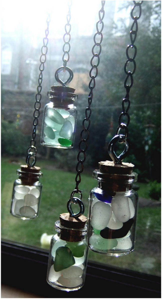 Pretty ornaments made by filling mini corked glass bottles with sea glass and hanging them from chain. Perfect for a window display.