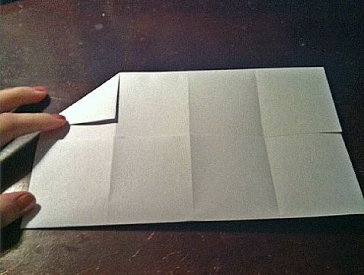Fold the top left corner to the first crease.