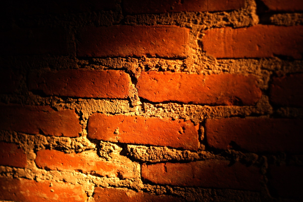 A brick wall partially illuminated by a ray of light. The light that separates the light from the dark.