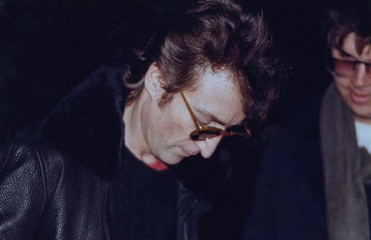 Lennon signing a copy of Double Fantasy for Chapman (right) several hours before the murder