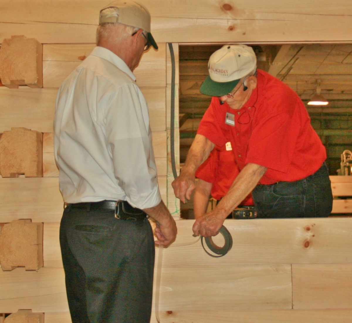 Appalachian Log Structures employees demonstrate the company's multiple techniques for sealing windows and doors.