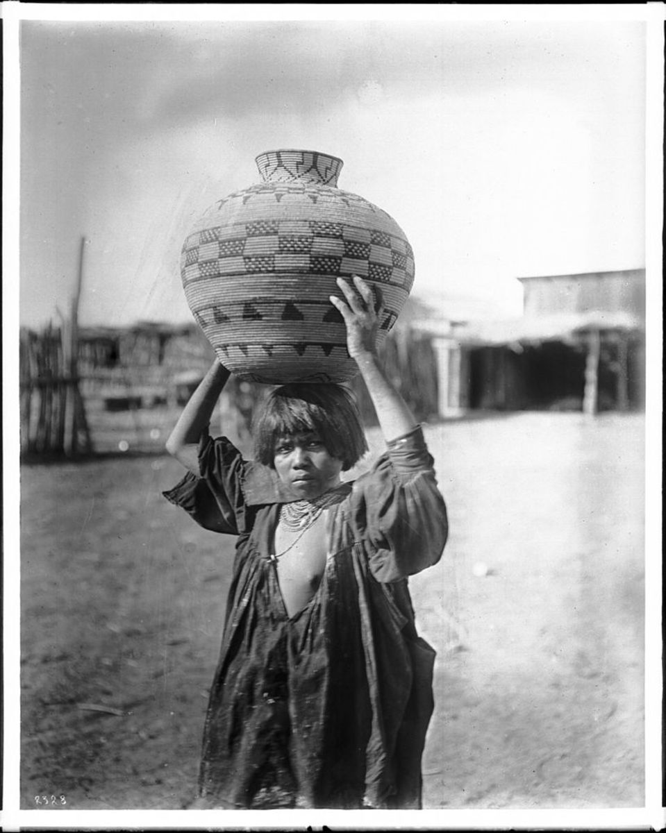 Apache Indian girl carrying an olla (a water basket) on her head, ca.1900