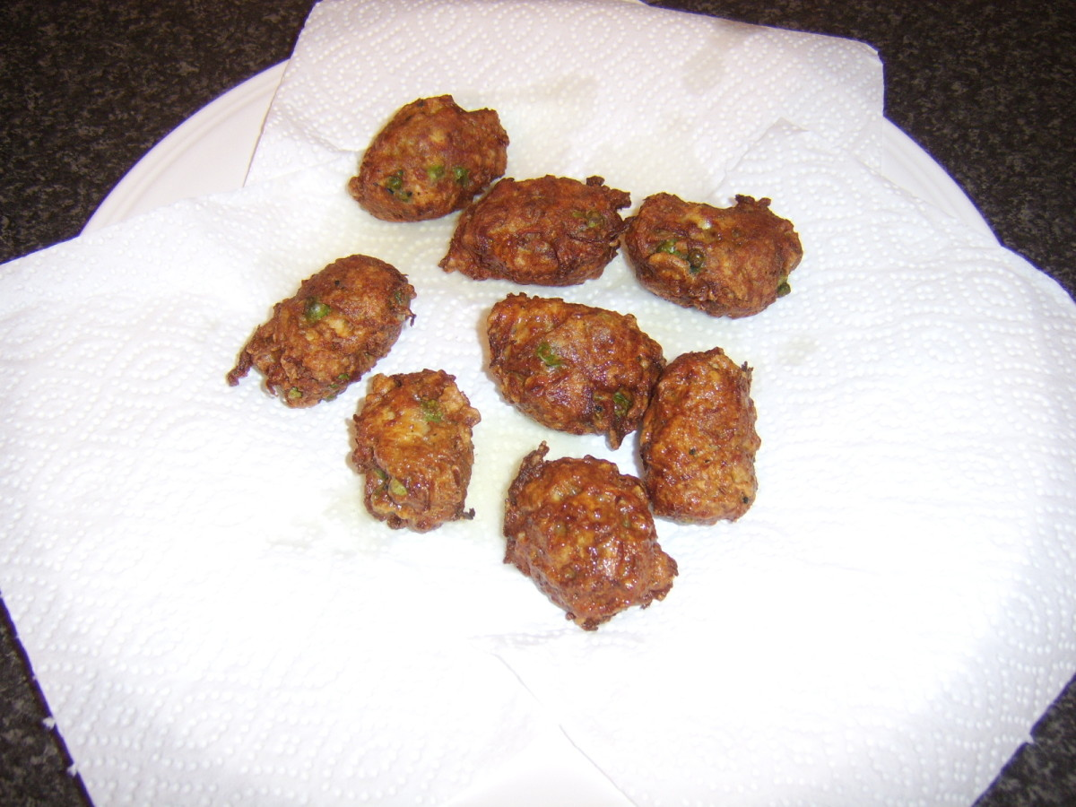 Pakora spiced chicken and vegetable fritters are drained on kitchen paper
