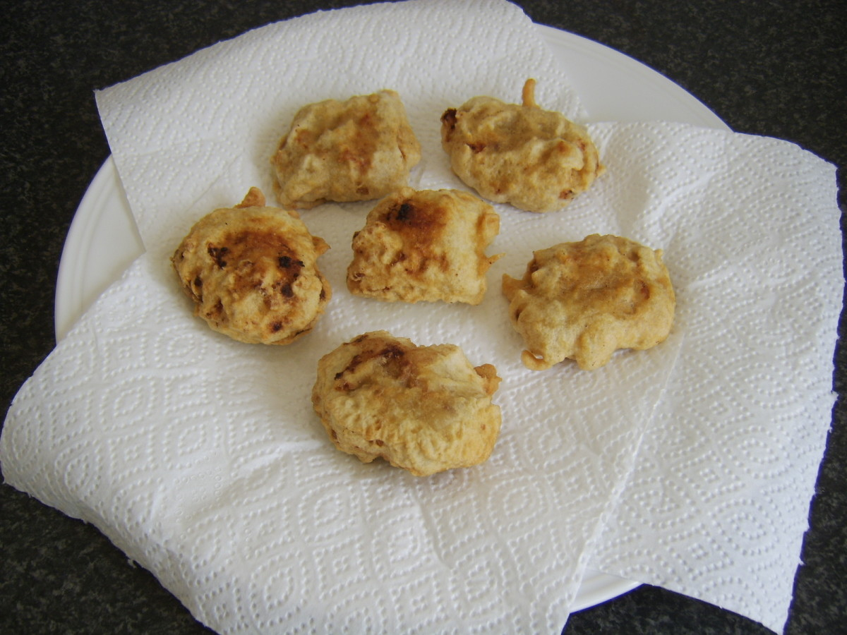 Spicy chicken and potato fritters are drained on kitchen paper
