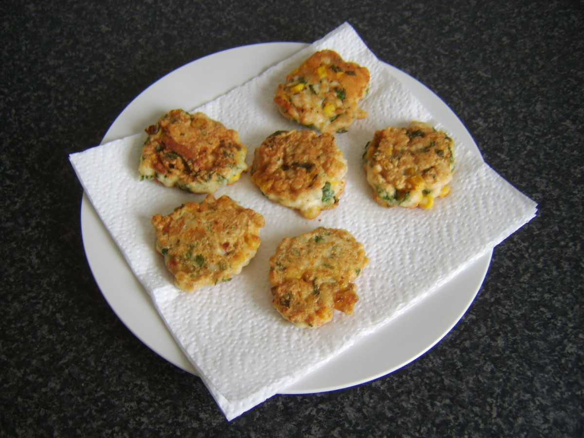 Chicken, sweetcorn and bell pepper fritters are drained on kitchen paper