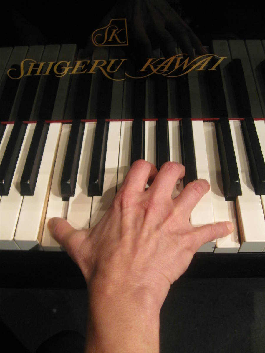 Woman's hand playing an octave on a full size piano. Notice the strain across the knuckles due to the stretching required to reach the notes.