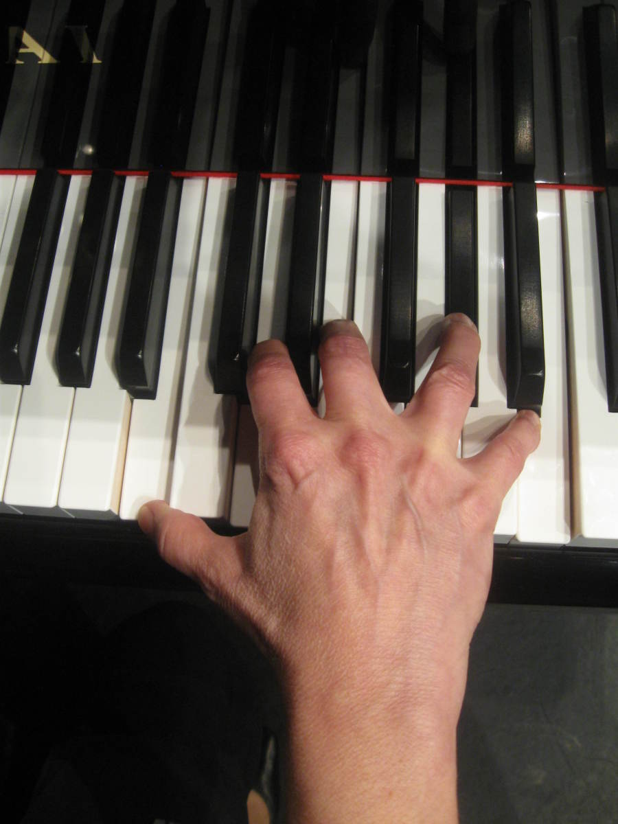 The same woman's hand playing a seventh chord on the slightly smaller 15/16th piano..