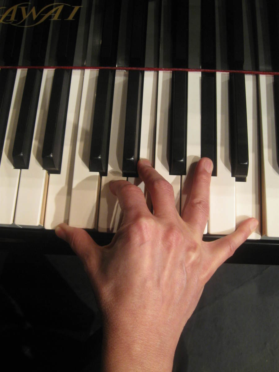 A woman with average sized hands playing a seventh chord on a full size piano. Note the strain of the hand and the awkward position of the fingers.