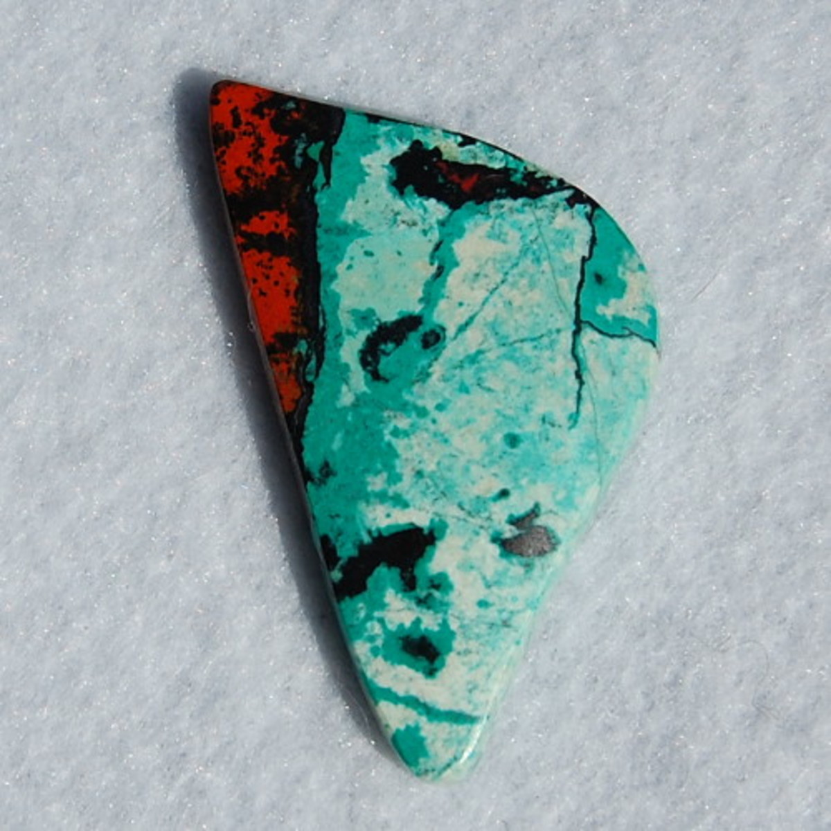 Sonoran Sunrise Chrysocolla cut by Marty Andersen.  This unique variety of gemstone gets it's color from Chrysocolla (blue), Cuprite (red) and Tenorite (black).