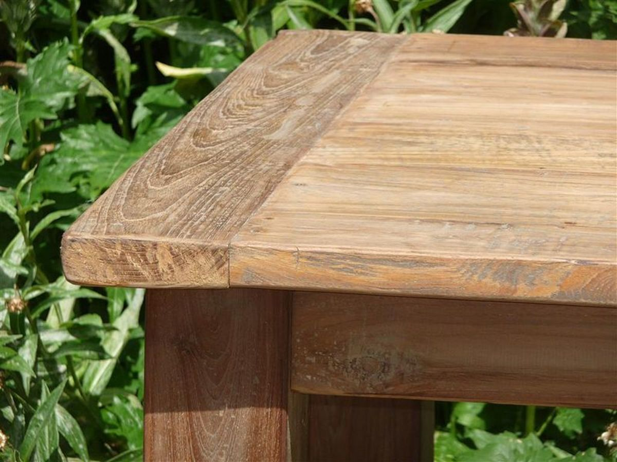 A teak wood table. Teak withstands almost any type of weather, and still looks beautiful. It is used extensively to make outdoor furniture for this reason.