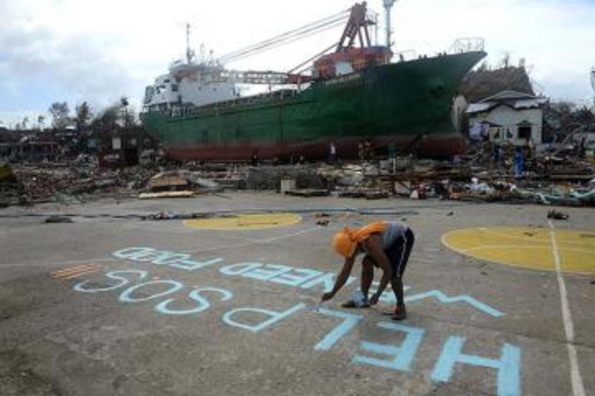 With a large ship washed away inland at the background, a victim writes on the ground asking for help hoping someone from above would see their desperation after Yolanda left the city in ruins...
