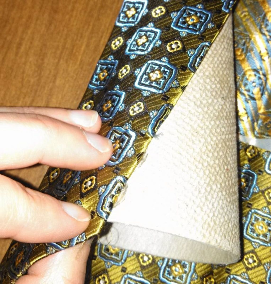 2) Start with one edge of the opened tie on the wider cone end, and use a thin bead of hot glue to fix the silk in place, all the way to the top.