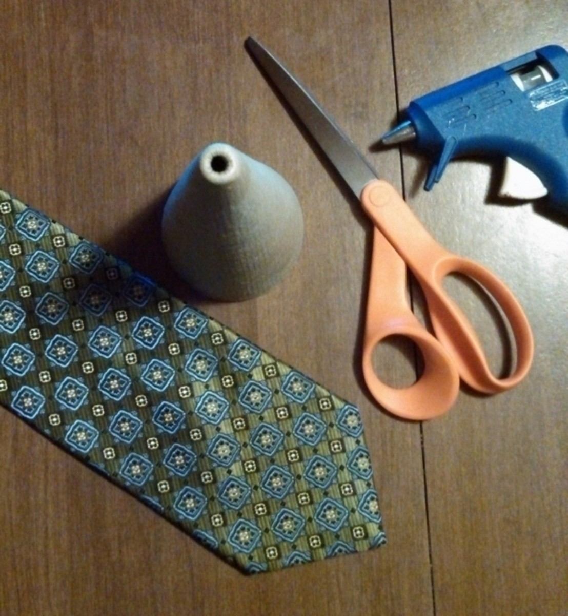 1) Gather your supplies. Cut the necktie at 10 inches from the widest point of the tie. Open the back seam. Remove tags and inside padding material.