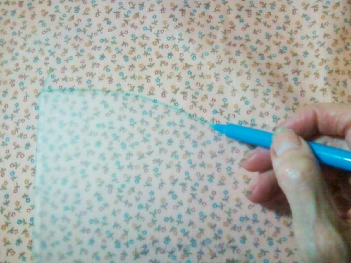 Marking the fabric with a water soluble pen and using the vinyl template as guide.