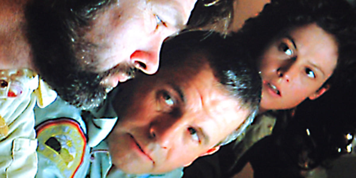 Ash and Ripley pay close attention to Captain Dallas as they discuss the Alien embryo