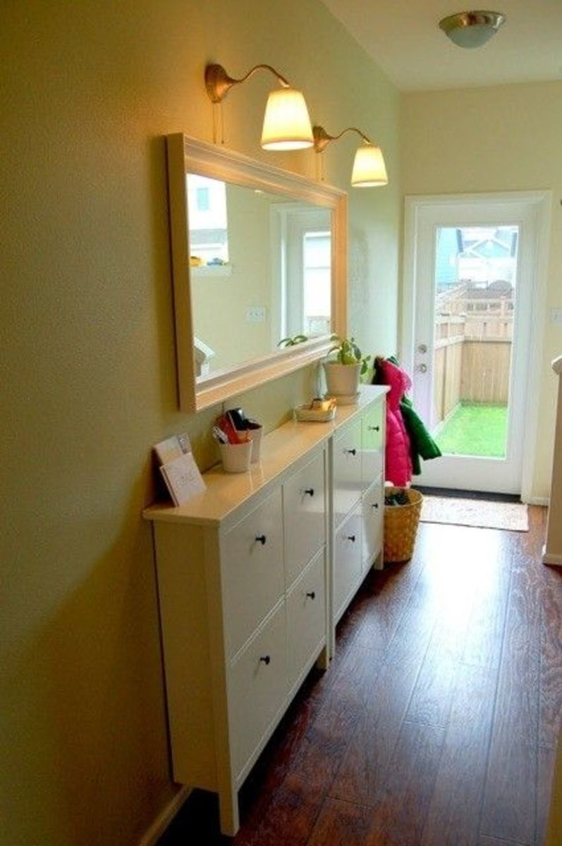 Remove the back legs to bring the cabinet closer to the wall.  Add a mirror and overhead lighting to make the room look larger.