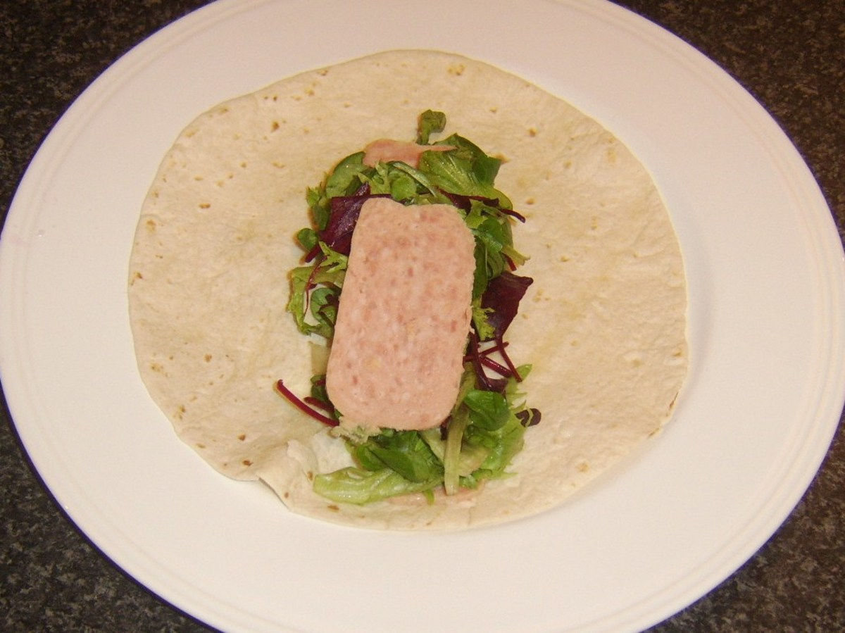 Spam and salad leaves arranged on wrap