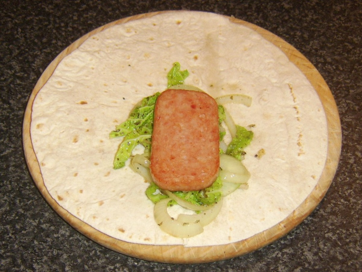 Spam slice tops cabbage and onion on tortilla wrap