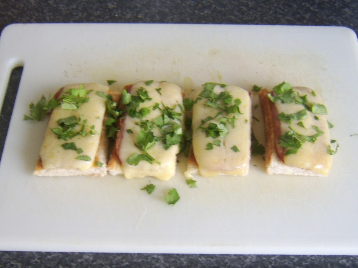 Coriander garnish is scattered on cheese and Spam finger bites