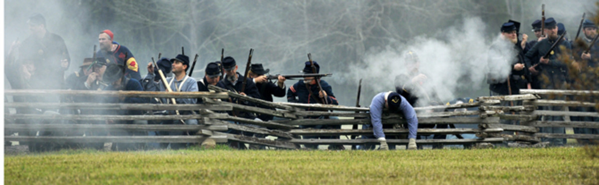 Living Historians fire from behind a wooden fence