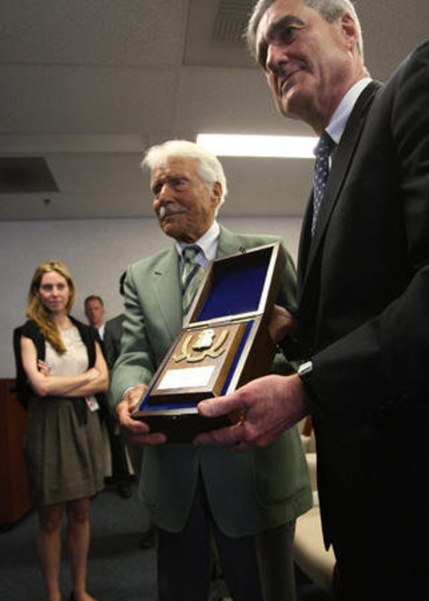 Granddaughter Alexis looks on as FBI director Robert Mueller show off the badge that was presented to the actor as an honorary special agent, the highest civilian honor awarded by the FBI, on June 8, 2009 in Los Angeles.