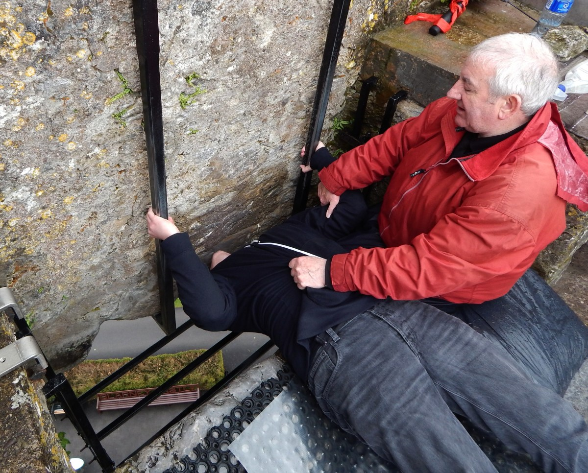 A visitor kissing the Blarney Stone, under the careful supervision of a guide whose job it is to keep adventurers safe.
