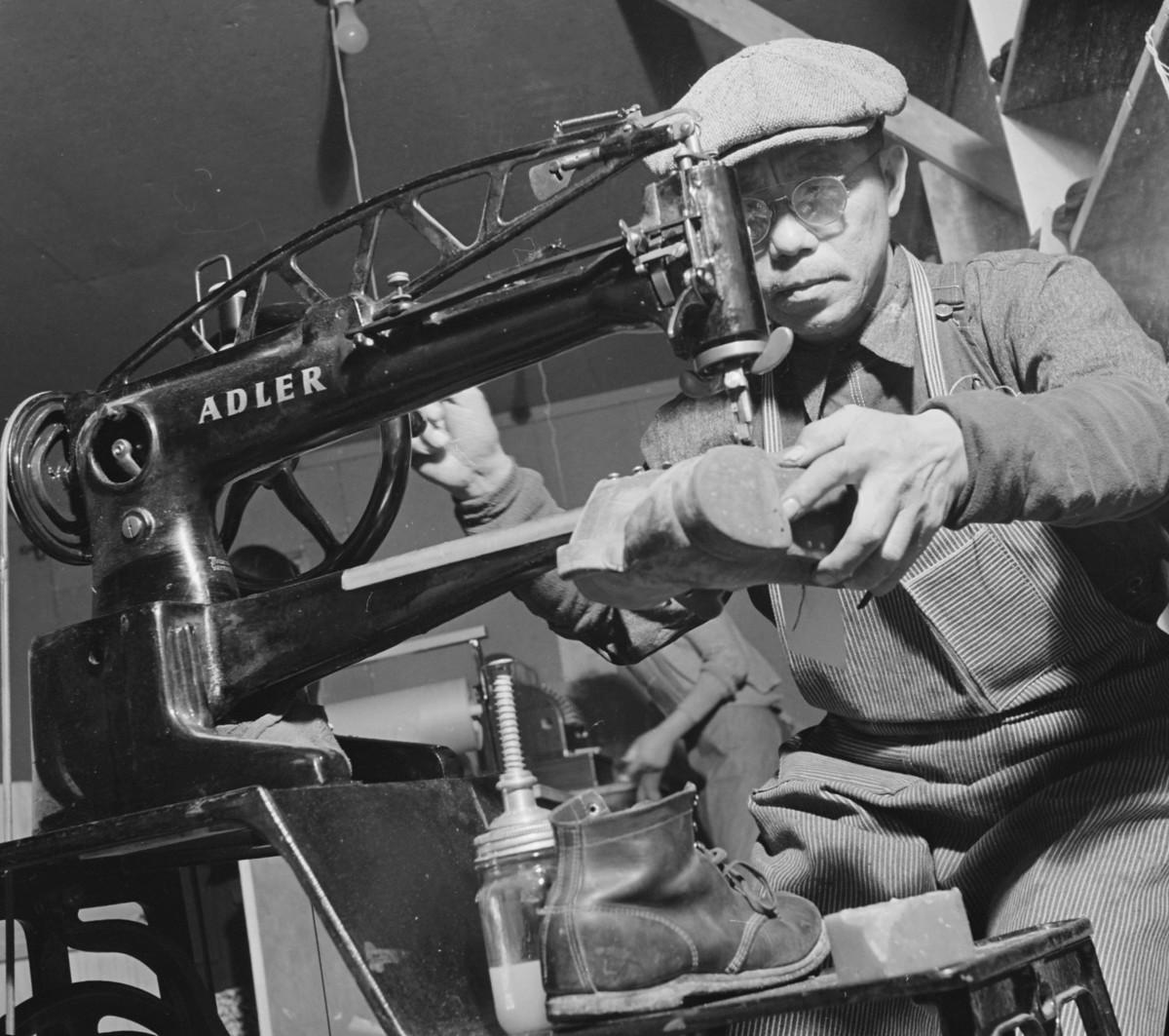 Cobbler operating a shoe stitching machine