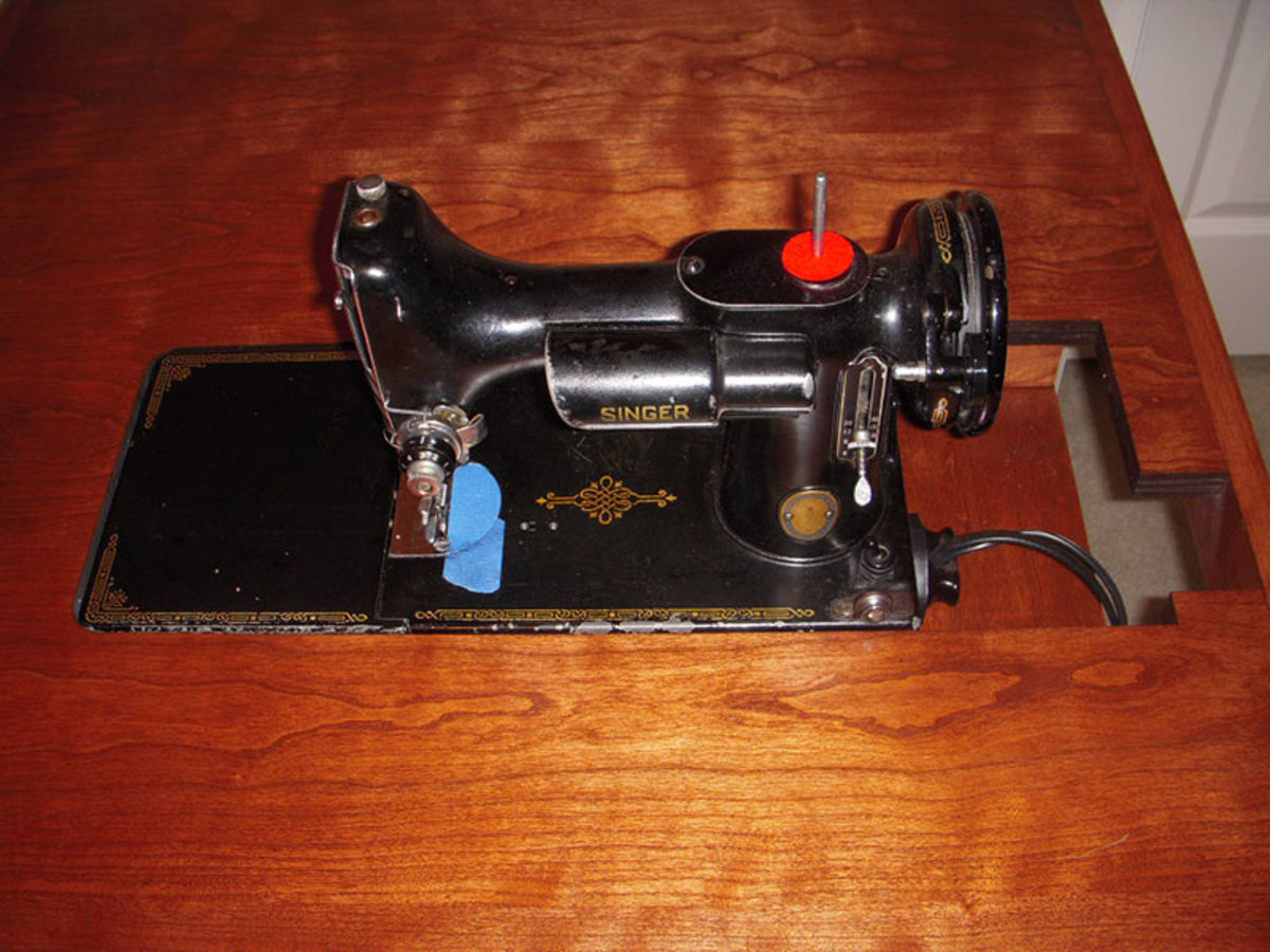 A singer 221 Featherweight sits in a table also made for the 301 machine.