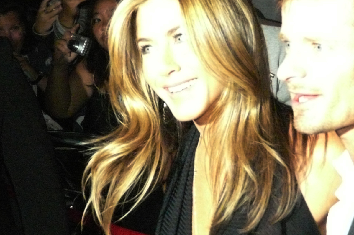 Aniston while she is surrounded by a crush of fans and press.