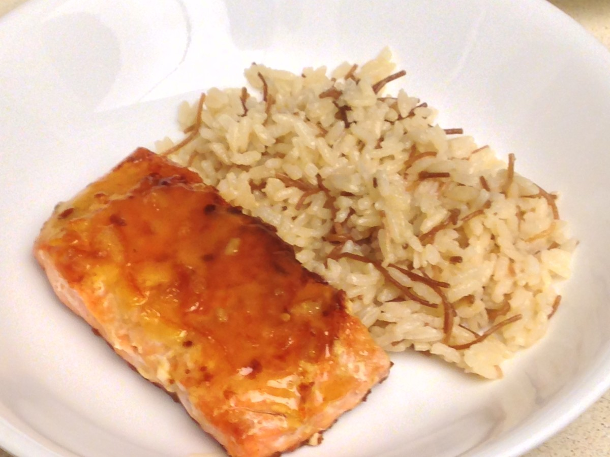 Pan seared salmon with a glaze of orange juice, lime juice, orange marmalade, and ginger.  Served with rice pilaf.