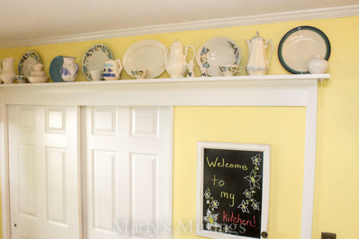 plate rail above a doorway with a chalk board for the kitchen