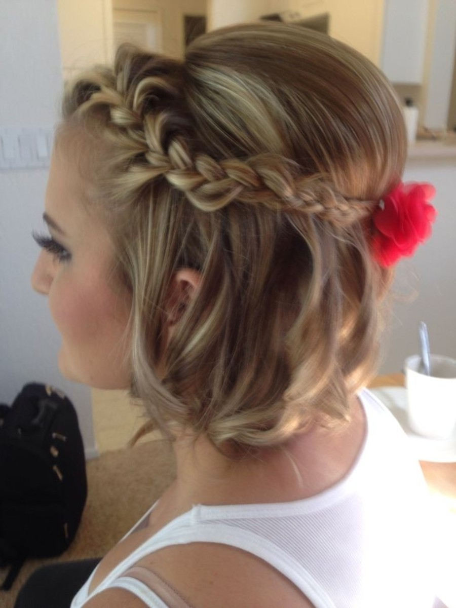 A simple updo with a teased crown, a halo braid, and curled hair.
