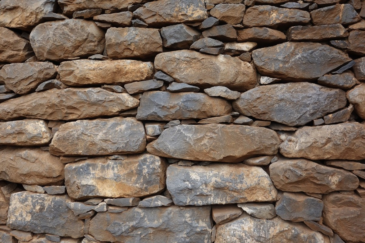 A dry-built stone wall is reminiscent of the layers of earth revealed in a road cut through a mountain, except that in a mountain cut, the layers extend for hundreds of feet or even miles