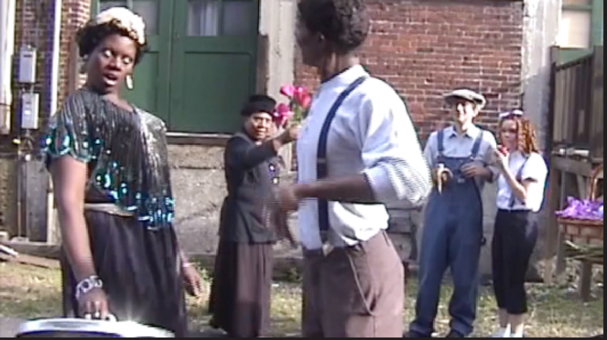 """This reenactment portrays Ma Rainey arguing with and giving a humiliating thrashing, with a garbage can top, to a man who allegedly cheated her in a dice game.  A """"flower lady"""" and other Beale Streeters look on in amazement."""