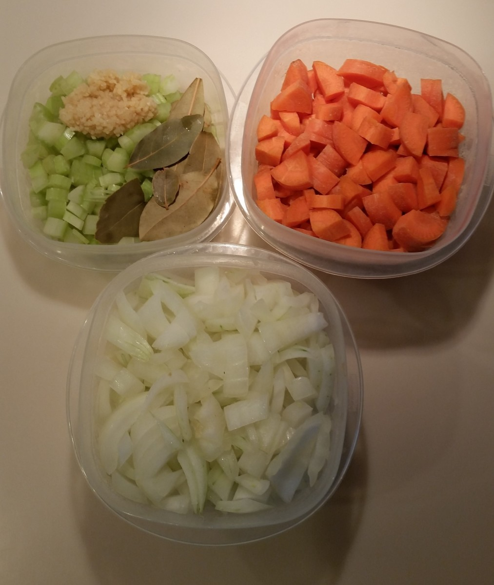 This shows the chopped carrots, chopped celery, chopped onions, some bay leaves and some chopped fresh garlic cloves.