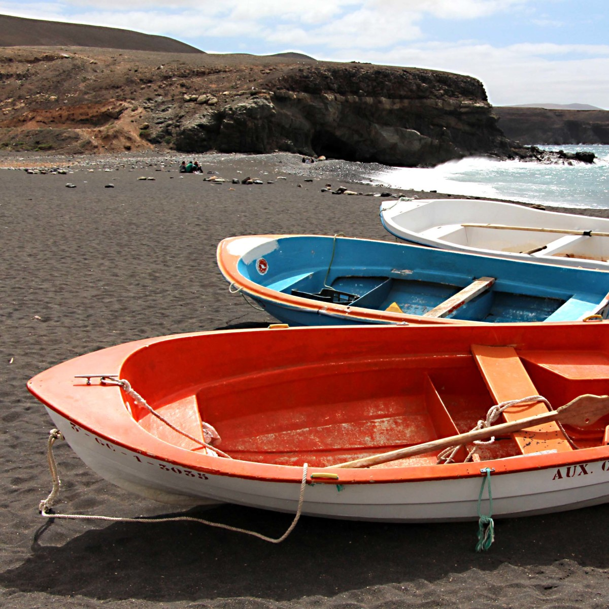 Red, blue and white rowing boats on the black sand beach of Ajuy on the western coast of Fuerteventura, a small village which is also shown elsewhere on this page