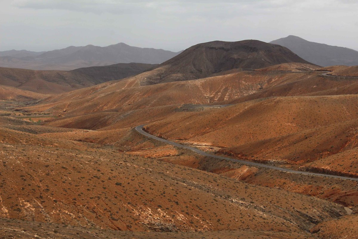 In south central Fuerteventura, the distinctive reddish landscape comprises low undulating hills for as far as the eye can see