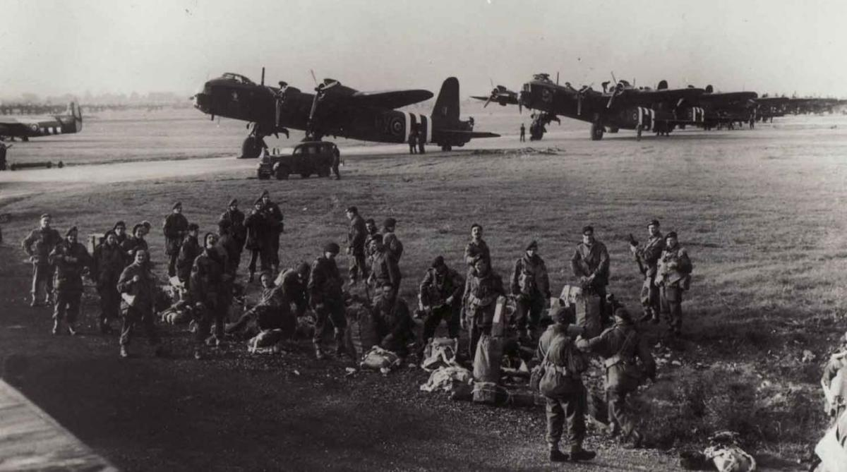 3. Platoon, 21st Ind. Parachute Coy. emplane at Fairford, Gloucester. Behind them are Short Stirling Bombers taken from bombing duties, assigned to tow gliders - vertical stripes were added to fuselages and wings for recognition as Allied aircraft