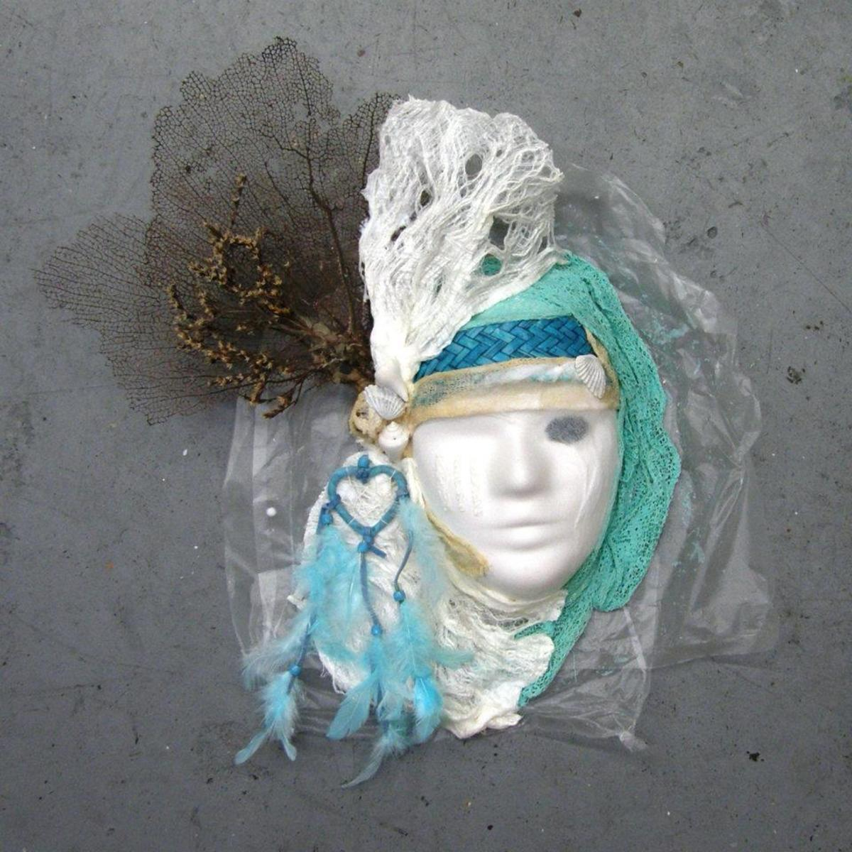Mask created using Paverpol and a paper mask, tree bark, beads and marine materials.