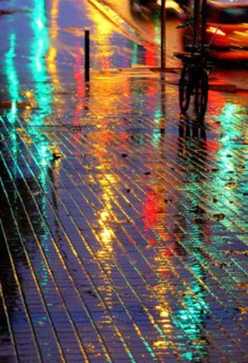 The lights reflected in the rain on the pavement look like splotches of paint.