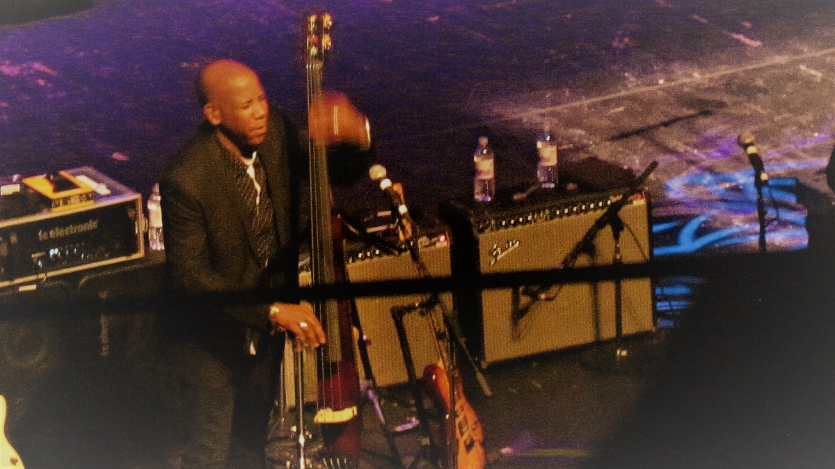 "Nathan East performs on bass as audience applauds during ""Fourplays"" performance."