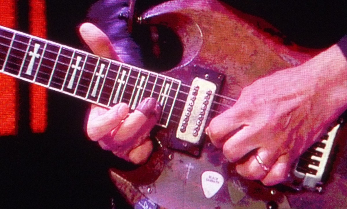 Notice Tony Iommi's fingerboard hand, and the false fingertips.