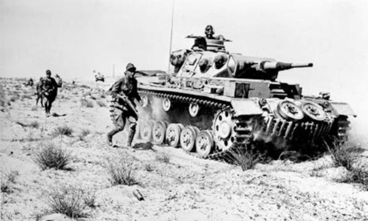 A German MKIII tank advancing along with infantry in North Africa.