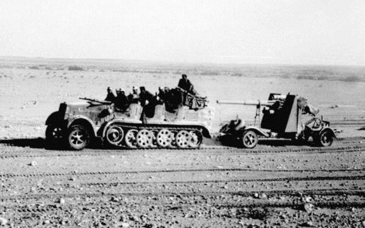 In North Africa, 8.8cm Flak 18 towed behind a Sd.Kfz. 7, with its side outriggers lifted for transport visible behind the gun shield.
